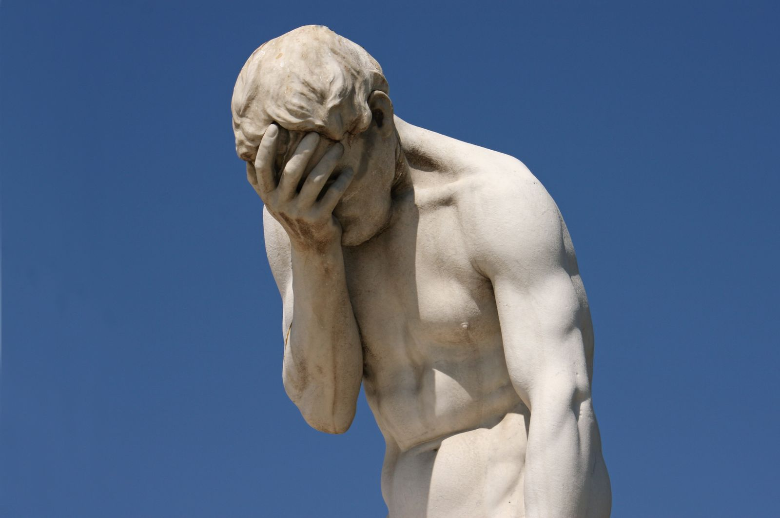 Facepalm: statue with head in hands