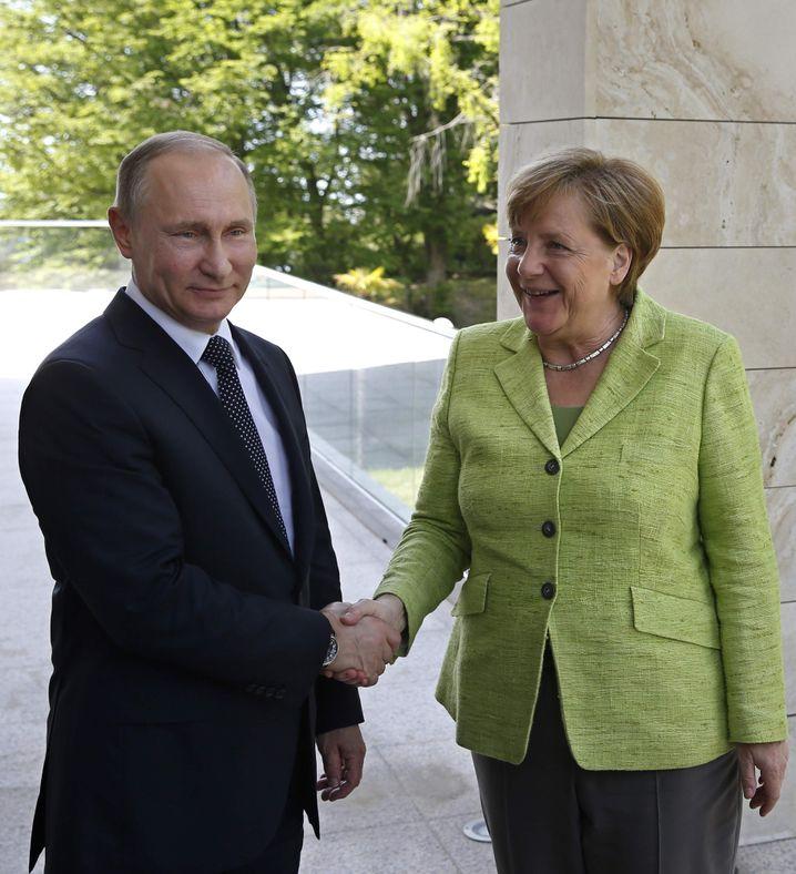 Sieht fröhlicher aus, als es war: Putin begrüßt Merkel