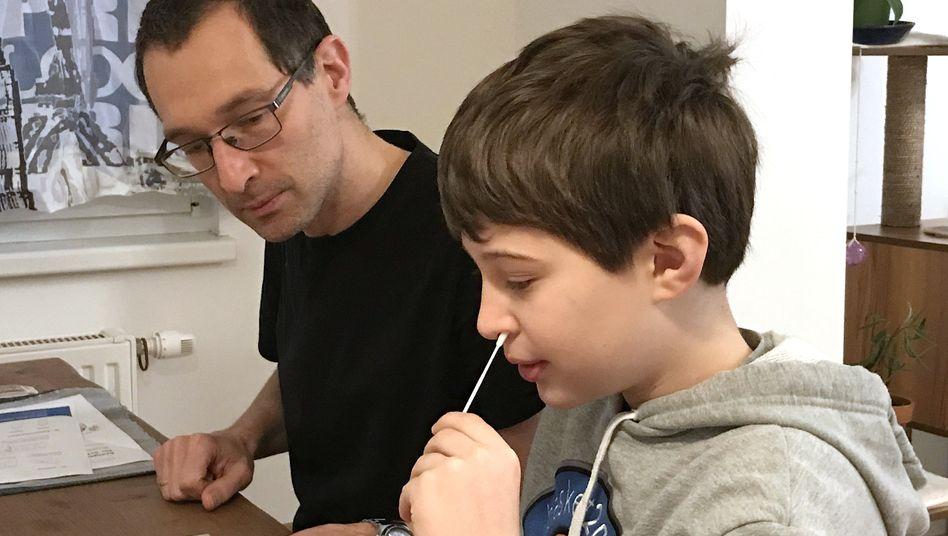 Ein Abstrich aus dem vorderen Nasenbereich reicht aus: Der neunjährige Tim beim Corona-Selbsttest (mit seinem Vater, in Wien)