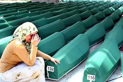 A Bosnian woman weeps next to the coffins of Muslim men and boys before their burial in Potocari, near Srebrenica.