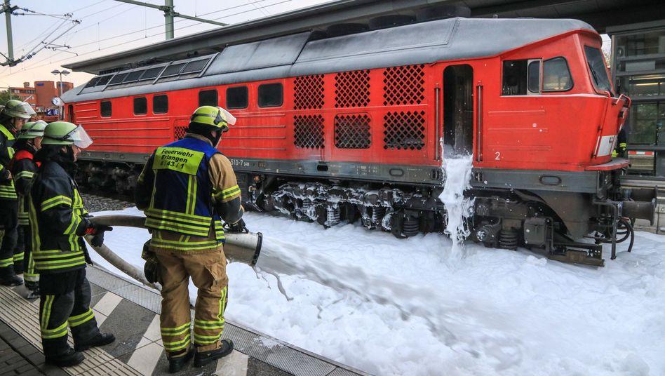 Einsatzkräfte der Feuerwehr Erlangen löschen mit Löschschaum eine brennende Lok