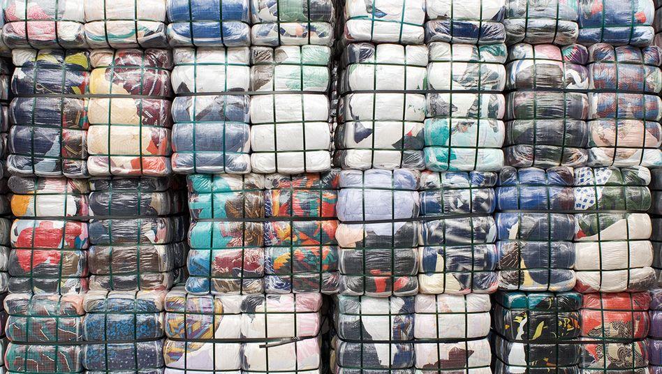 """Für den Export verpackte und gestapelte Altkleider auf einem Prospekt der Textil-Recycling GmbH: """"Das wäre das Ende der kostenlosen Textil-Entsorgung - und der gemeinnützigen Altkleiderspende"""""""
