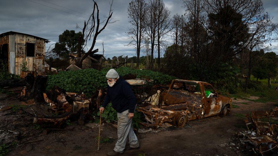 Jim Humphries geht an Trümmern vorbei, die die jüngsten Buschbrände hinterlassen haben