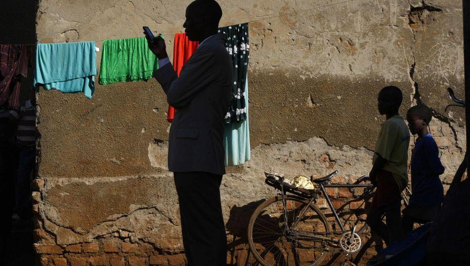 Ugander mit Smartphone (Symbolbild)