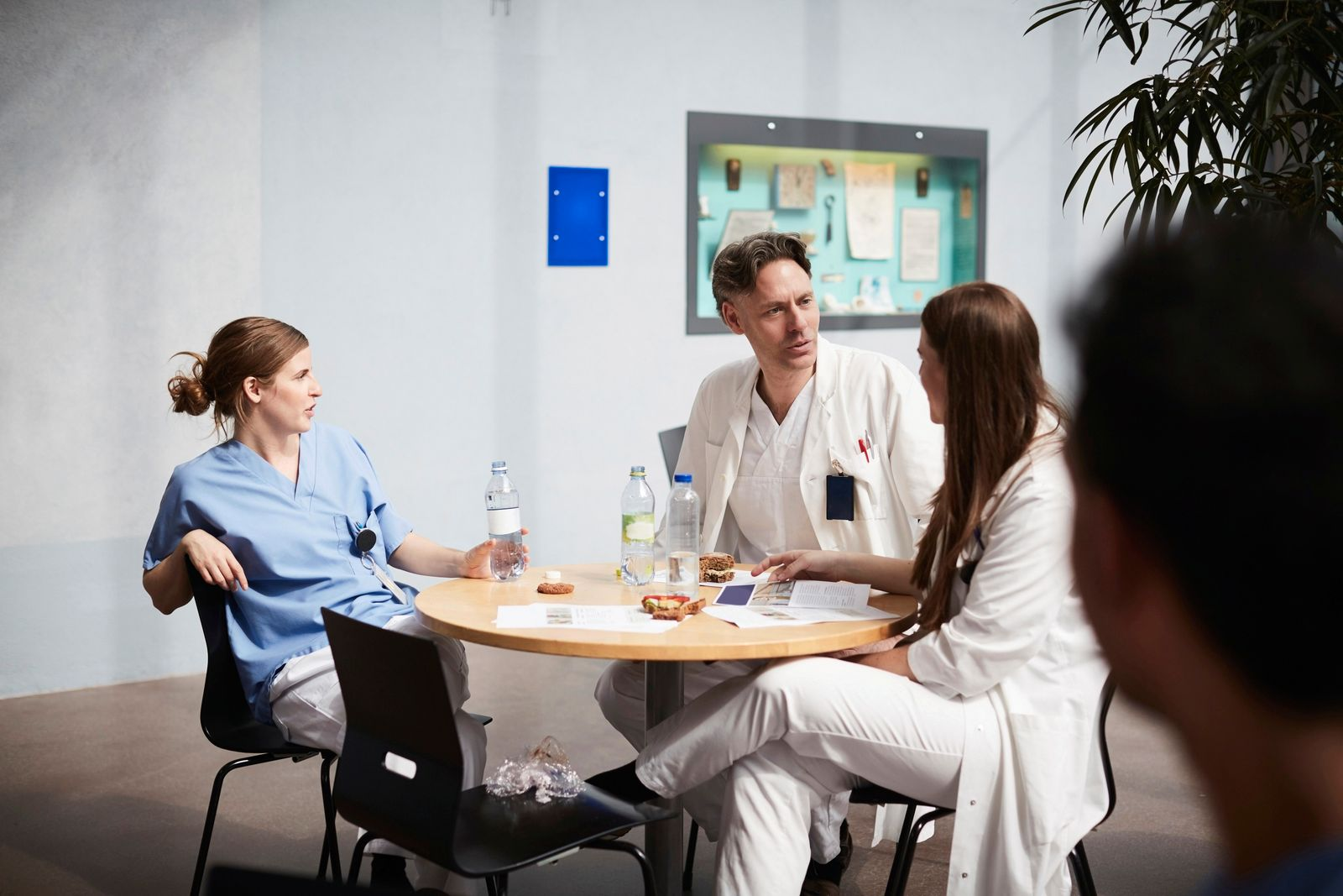 Confident mature doctor discussing with female coworkers while sitting at table in hospital cafeteria