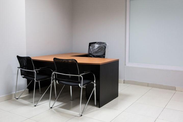 Beratungszimmer im Jobcenter: Graue Wände, schwarzes Mobiliar, ein paar Infoblättchen - alles wie in Deutschland