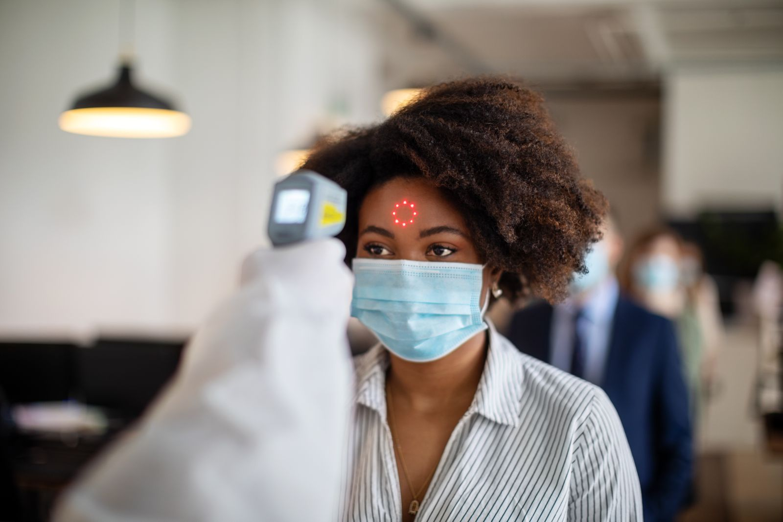 Woman going through a temperature check before going to work in office