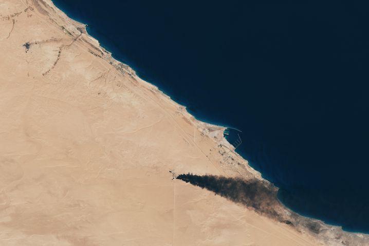 """Schwarzer Rauch: Diese Aufnahme von """"Sentinel 2"""" zeigt einen brennenden Öltank nahe des Hafens Ras Lanuf. Das Tanklager As-Sidr ist oben links als schwarzer Fleck in der Wüste zu erkennen."""