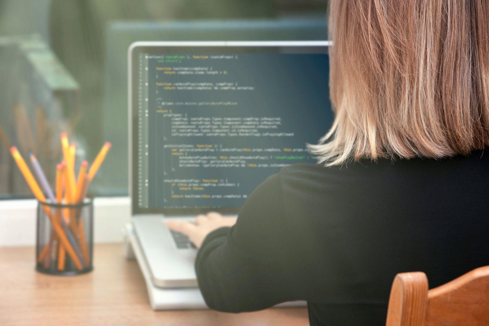 woman freelance programmer working from home. website code on screen. (Esermulis)