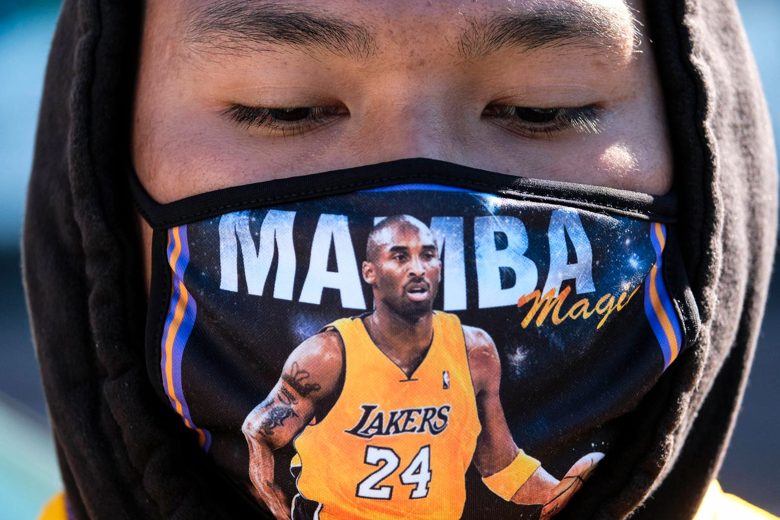 January 26, 2021, Los Angeles, California, USA: A fan wearing a face mask is seen in front of a makeshift memorial hono
