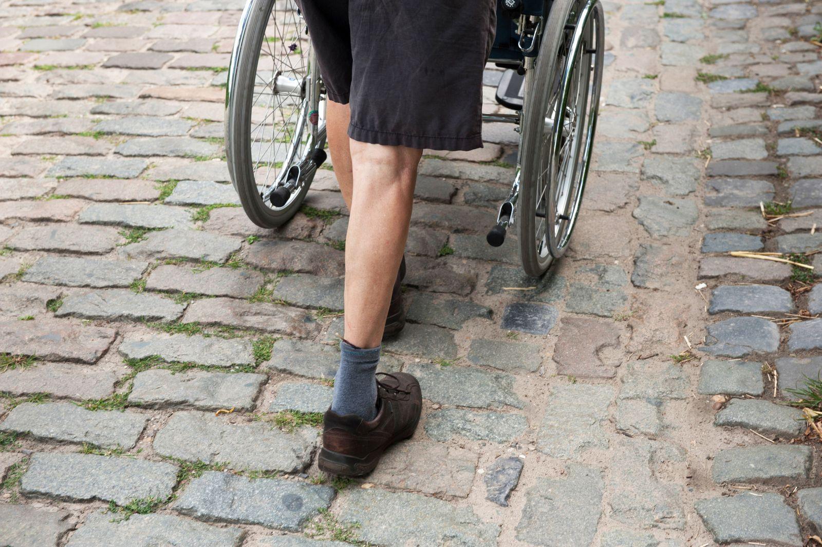 Mann schiebt einen Rollstuhl