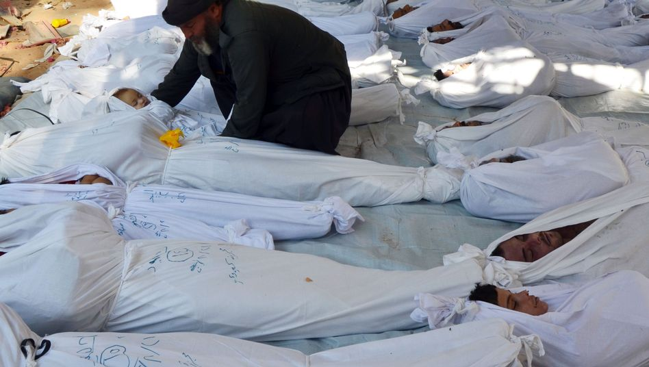 A man holds the body of a child allegedly killed by a nerve gas attack in Syria on Wednesday.