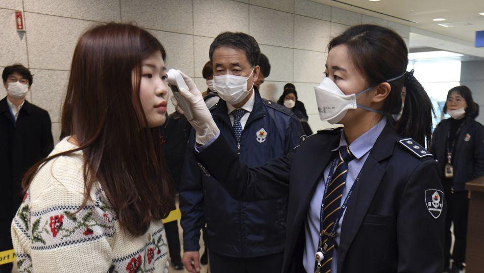 Eine Quarantänebeamtin überprüft die Körpertemperatur von Passagieren am Flughafen Incheon