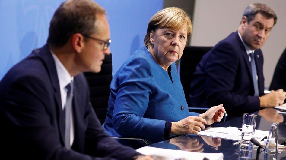 Kanzlerin Angela Merkel mit Berlins Regierendem Bürgermeister Müller (l.) und dem bayerischen Ministerpräsidenten Söder