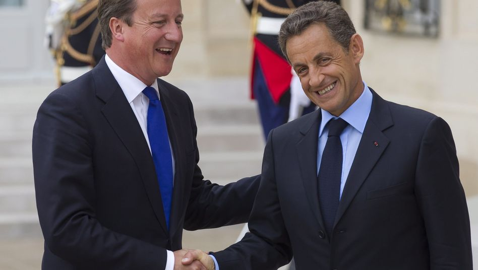 French President Nicolas Sarkozy (right) greets British Prime Minister David Cameron on Thursday at the Elysee Palace.