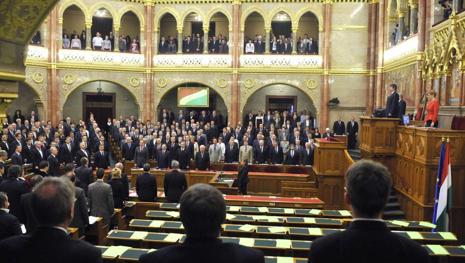 Hungarian lawmakers sing the national anthem after the ruling alliance of the Fidesz party and Christian Democrats approved Hungary's new constitution in parliament on Monday.