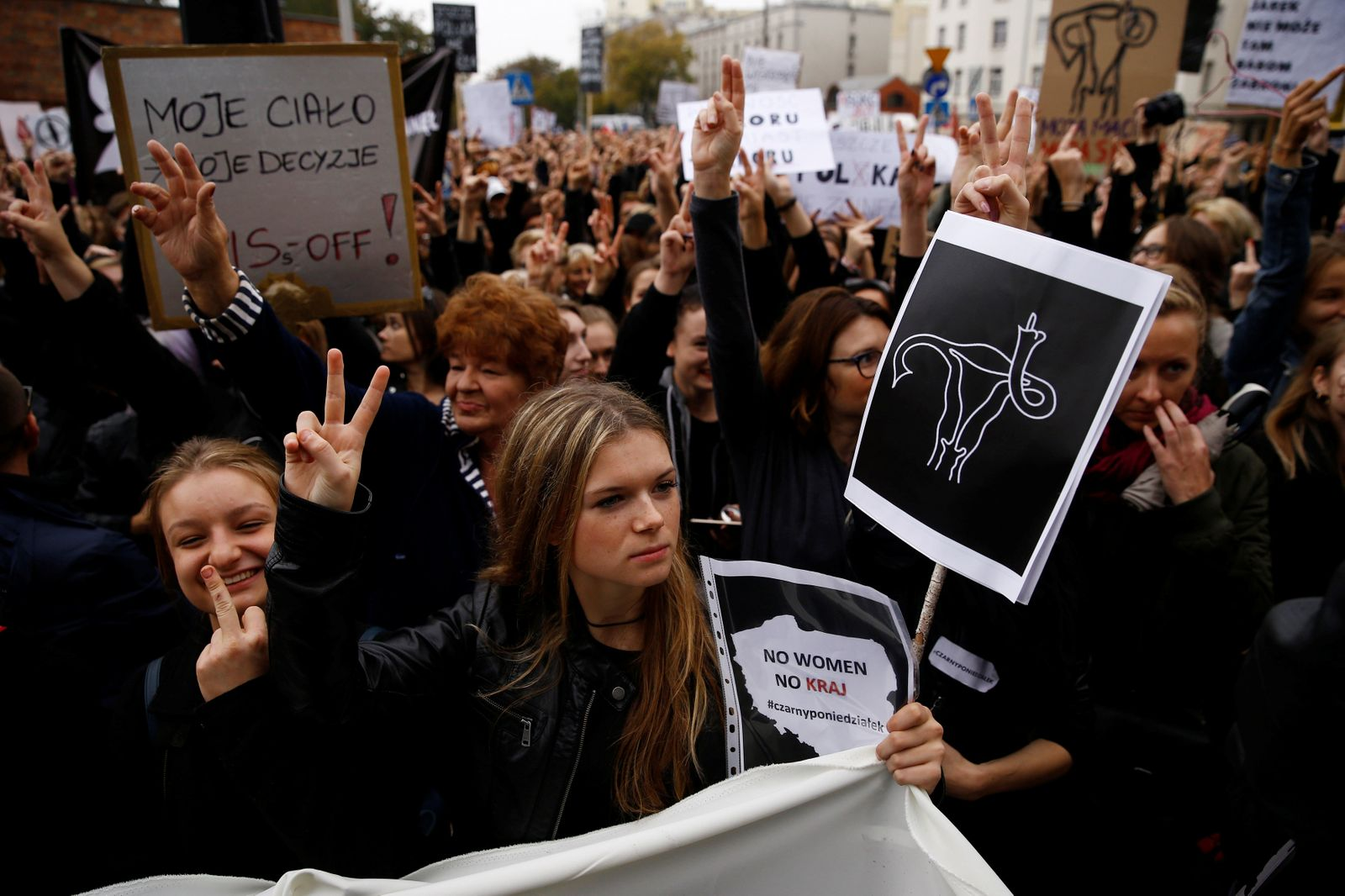 Women gesture as people gather in an abortion rights campaigners' demonstration to protest against plans for a total ban on abortion in front of the ruling party Law and Justice (PiS) headquarters in Warsaw