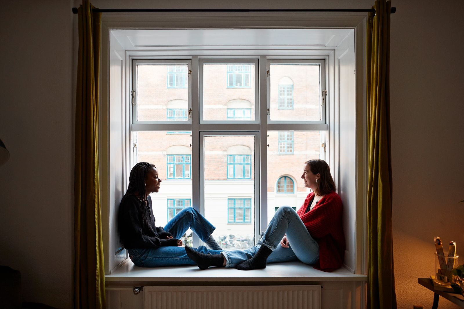 Young female roommates talking in apartment window