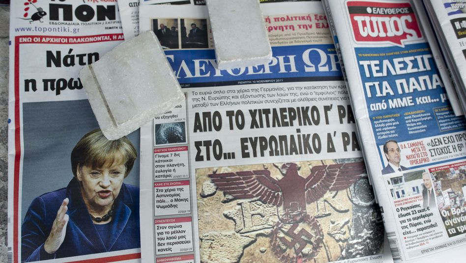 "A Greek newspaper is shown on Thursday, Nov. 10, featuring the headline: ""From Hitler's Third Reich to Europe's Fourth Reich"""