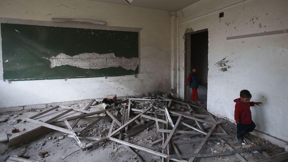 Kinder in einem zerstörten Klassenraum in Ost-Ghuta