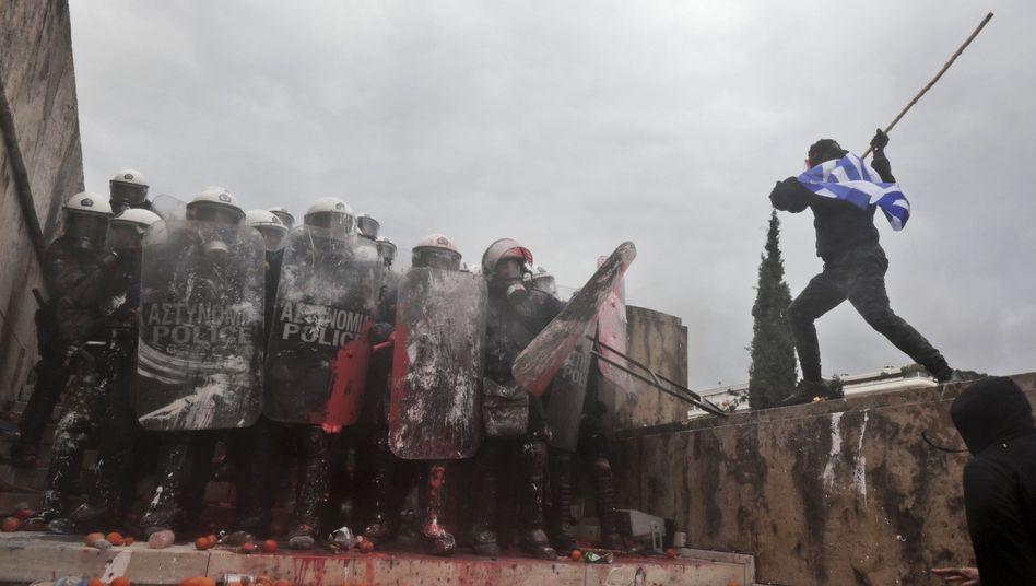 Ein Demonstrant attackiert Polizisten