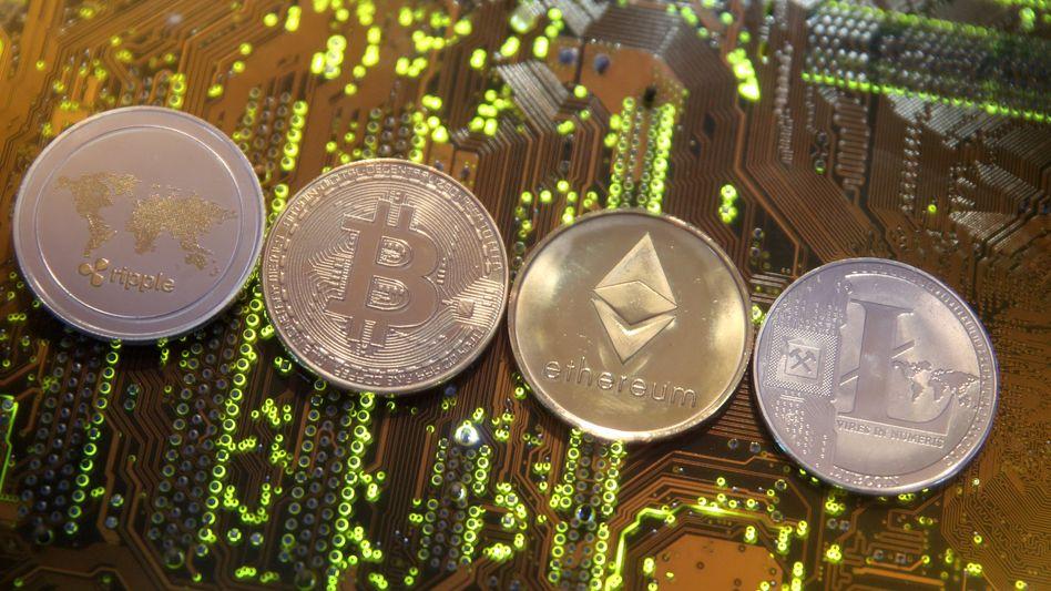 Symbolmünzen der Kryptowährungen Ripple, Bitcoin, Etherum und Litecoin