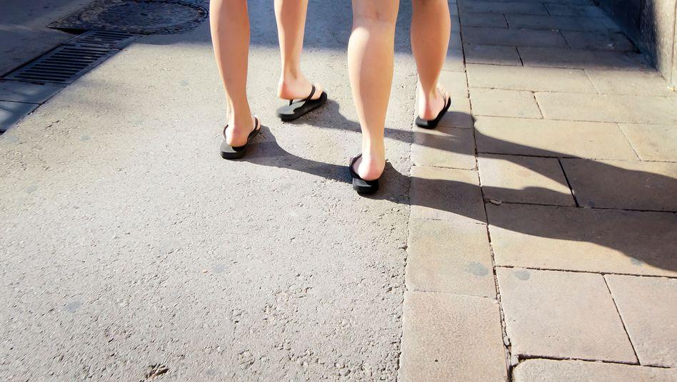 Platsch, platsch, platsch: Der unheilvolle Dreiklang aus nackten Füßen, Gummisohlen und Asphalt