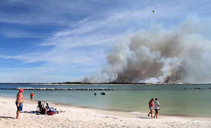 Beach goers enjoy St. Andrews State Park in Florida with smoke from controlled fires on the horizon in March 2016.