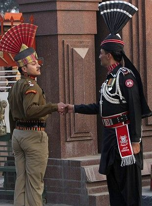 """Pakistani (r) and Indian border guards shake hands during the """"Beating the Retreat"""" ceremony at the India and Pakistan joint border."""