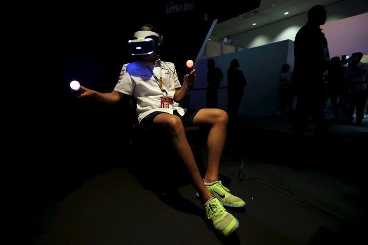 Ein Spieler testet Project Morpheus: Er taucht in die Spielewelt ein, Außenstehende sehen ihn nur wild mit den Controllern in der Hand fuchteln