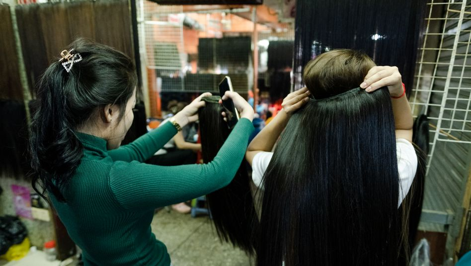 Two women in Phnom Penh check out extensions made of real human hair: The hair often comes from poor women in rural areas.