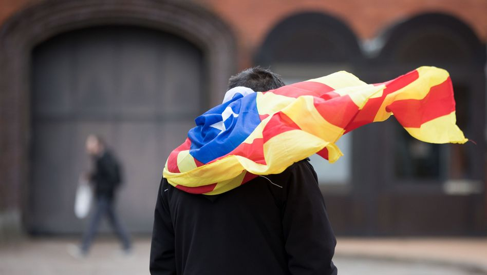 A Puigdemont supporter waves a Catalan independence flag at a jail in Neumünster.