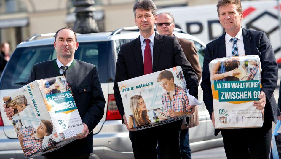 Politiker der Partei Freie Wähler tragen Kisten mit Unterschriften zum Innenministerium in München