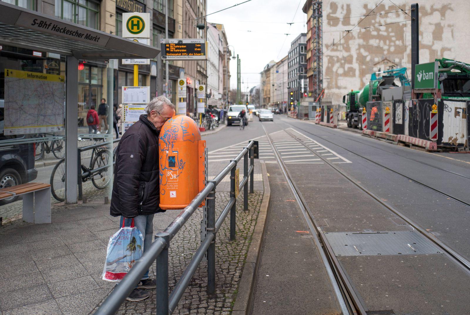 Ein aelterer Mann sucht in einem oeffentlichen Muelleimer nach Pfandflaschen. 24.02.2020, Berlin, GER - Ein aelterer Man