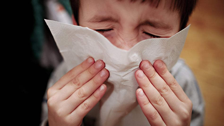 Kleiner Junge niest in ein Taschentuch (Archivfoto)