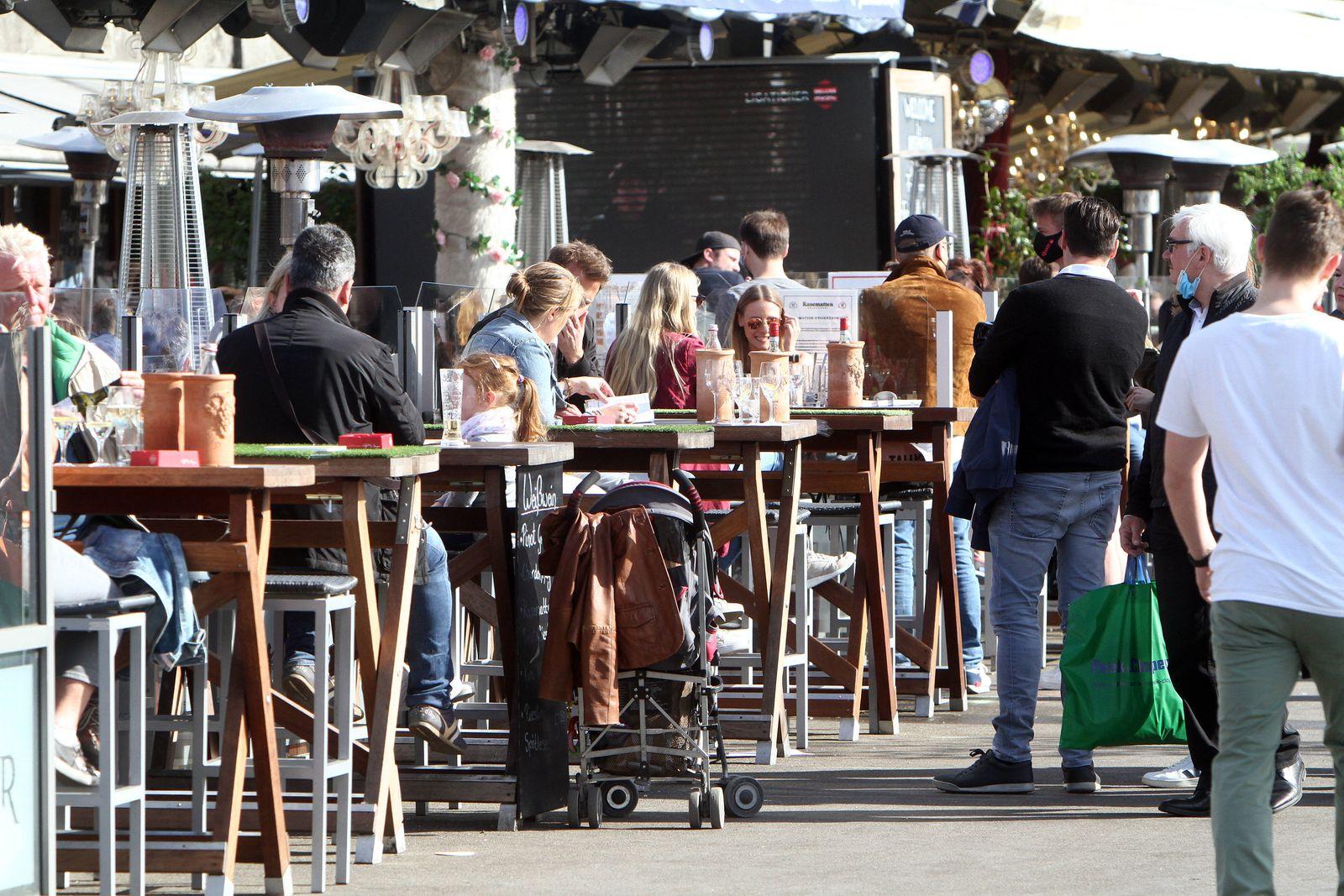 Auf Einlass wartende Gäste stehen vor einem geöffneten und voll besetzten Restaurant in den Kasematten auf der Uferprome