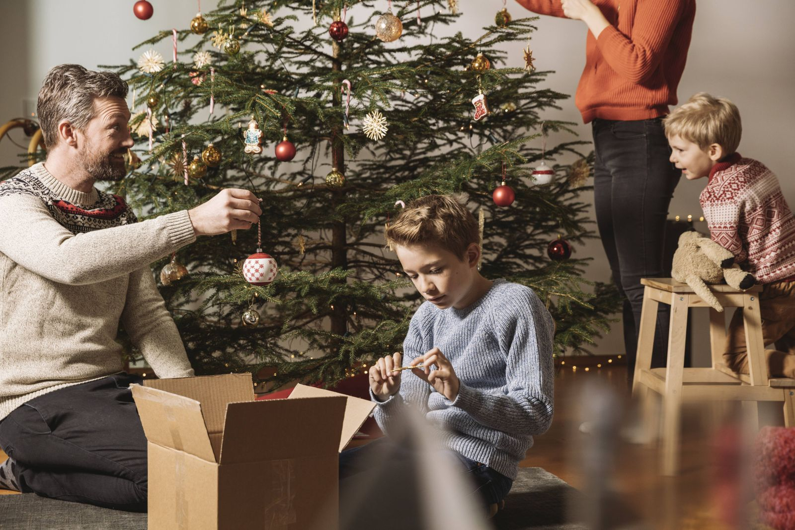 Family decorating Christmas tree model released Symbolfoto property released PUBLICATIONxINxGERxSUIx