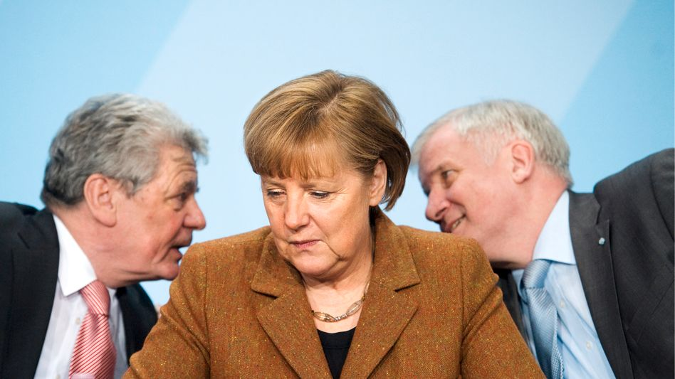 Horst Seehofer, the head of Bavaria's Christian Social Union, and Germany's presidential candidate Joachim Gauck, banter behind Chancellor Angela Merkel's back.