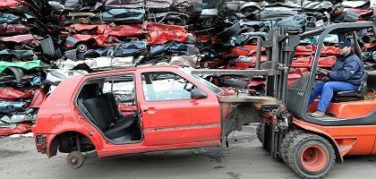 Ich bin eine Prämie: Ein nicht mehr gebrauchsfähiges Fahrzeug wird zur Schrottpresse gefahren.