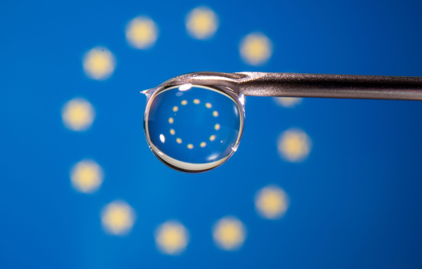 The EU flag is reflected in a drop on a syringe needle in this illustration