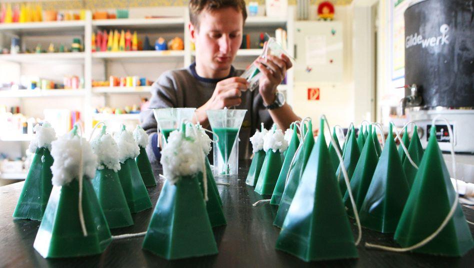 Ein Mitarbeiter in einer Werkstatt für Behinderte in Magdeburg bei der Produktion von Wachskerzen