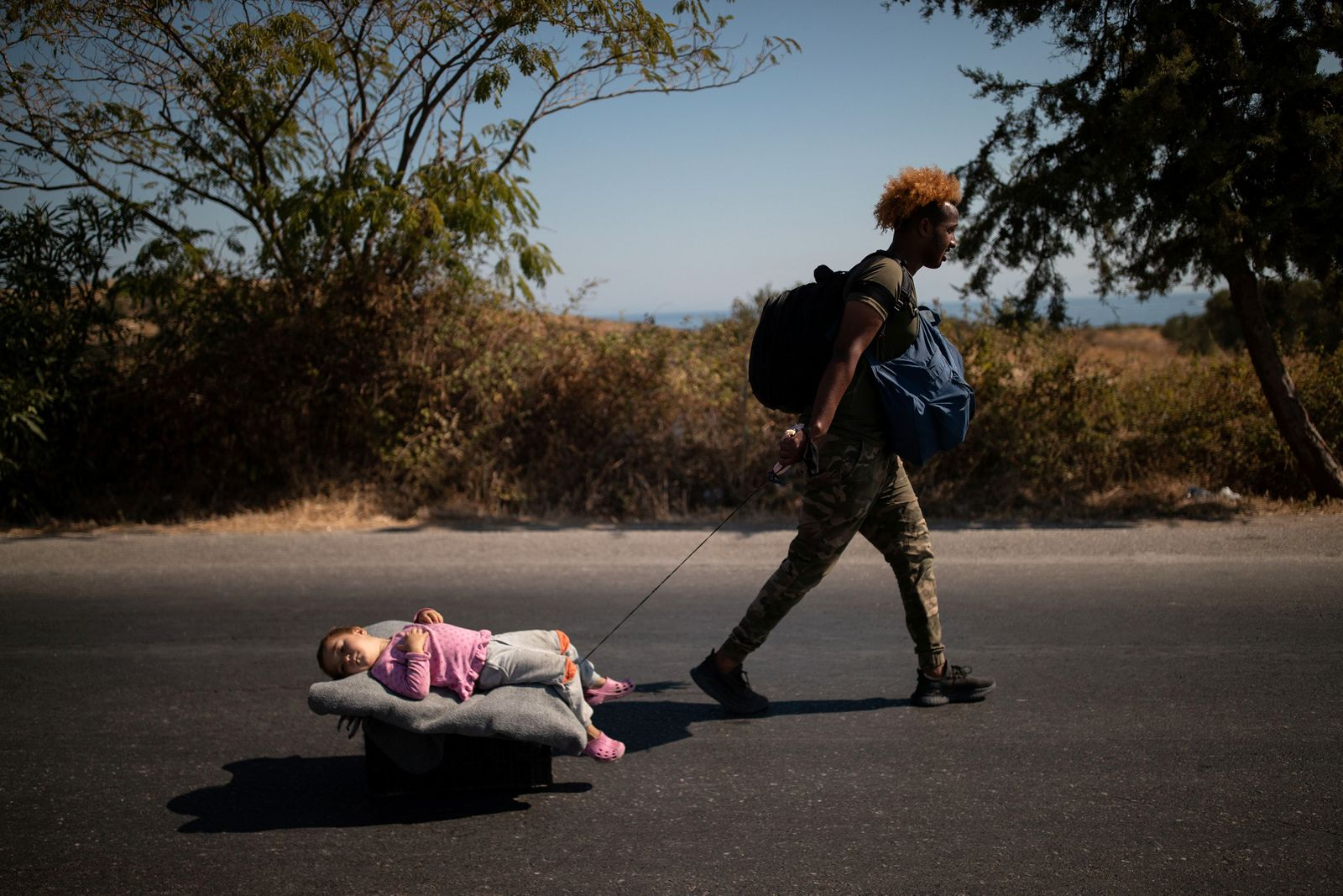 Migrant pulls a girl lying on a cart, following a fire at the Moria camp on the island of Lesbos