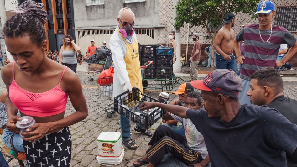 Catholic priest Julio Lancellotti handing out breakfast to the homeless in the Mooca district of São Paulo.