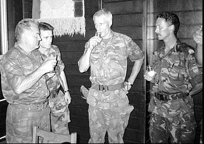 Bosnian Serb army Commander General Ratko Mladic, left, drinks a toast with Dutch UN Commander Tom Karremans, second right, while others unidentified look on in village of Potocari, some 5 kilometers north of Srebrenica Wednesday, July 12, 1995.