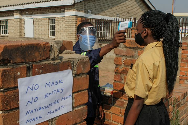 Bei einer Schülerin wird die Temperatur gemessen, bevor sie ihre Schule in Simbabwes Hauptstadt Harare betreten darf