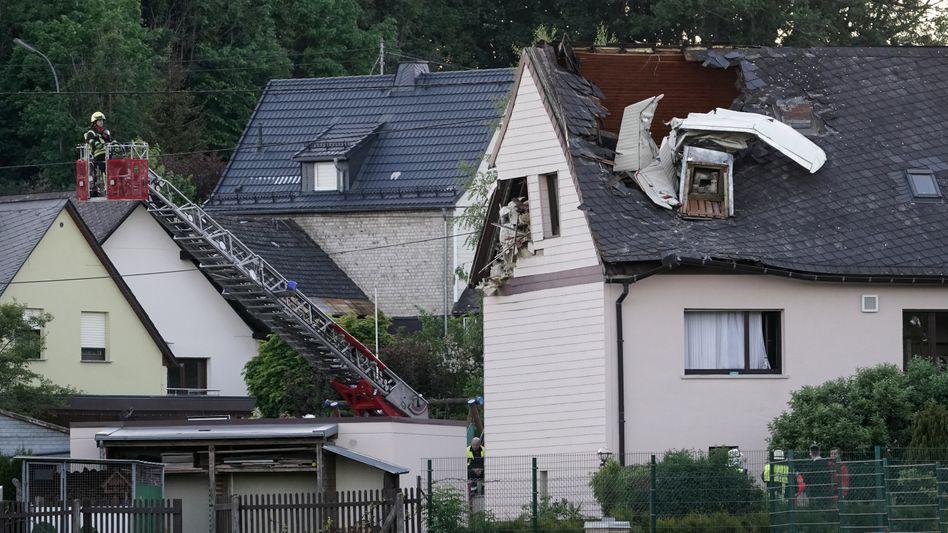 Wrackteile ragen aus dem Dach eines Wohnhauses in Langenhahn: Der Pilot überlebte den Absturz