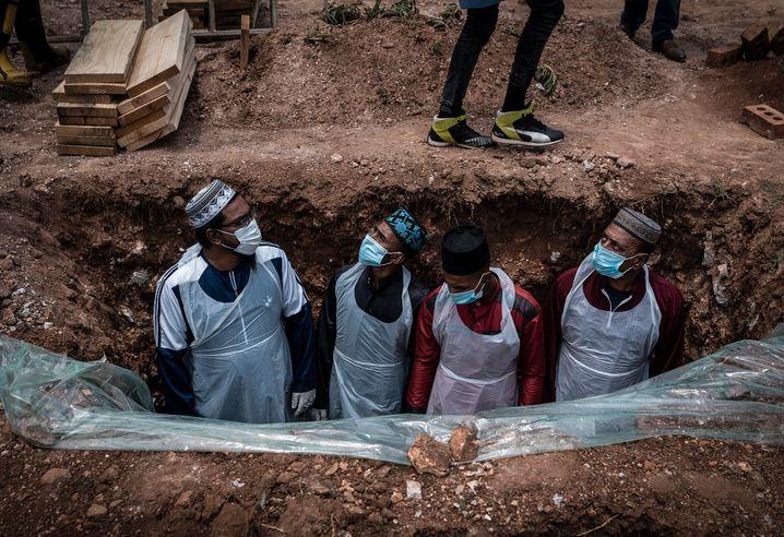 Bestatter in Schutzkleidung bereiten das Grab für eine an dem Coronavirus verstorbenen Person für die Beerdigung vor