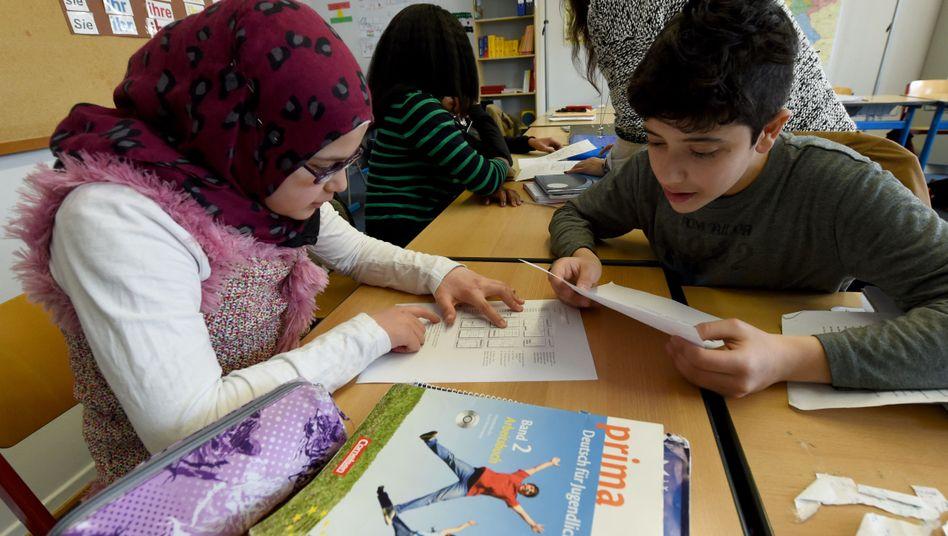 Bessan und Wasim aus Syrien im Unterricht: Bei der Lesekompetenz holen Migrantenkinder auf