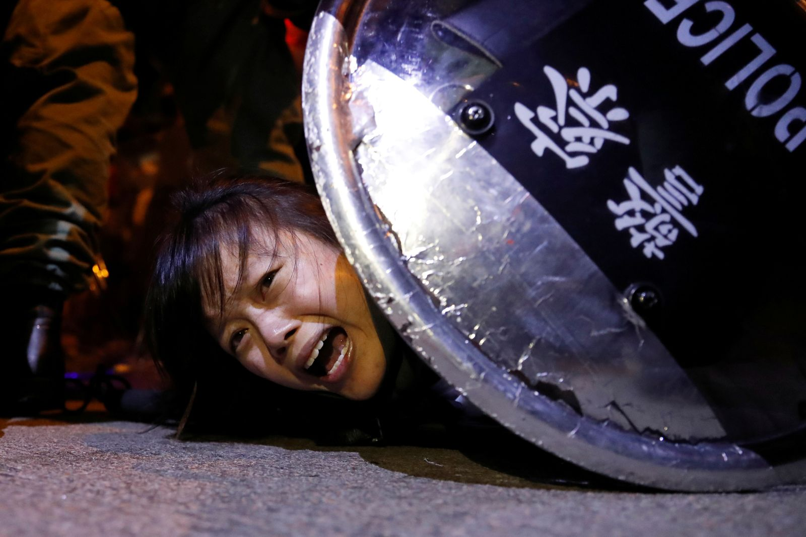 An anti-extradition bill protester is detained by riot police during a protest outside Mong Kok police station, in Hong Kong
