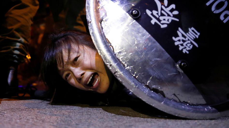 Eine Regierungsgegnerin wird im September 2019 in Hongkong von der Polizei ergriffen.